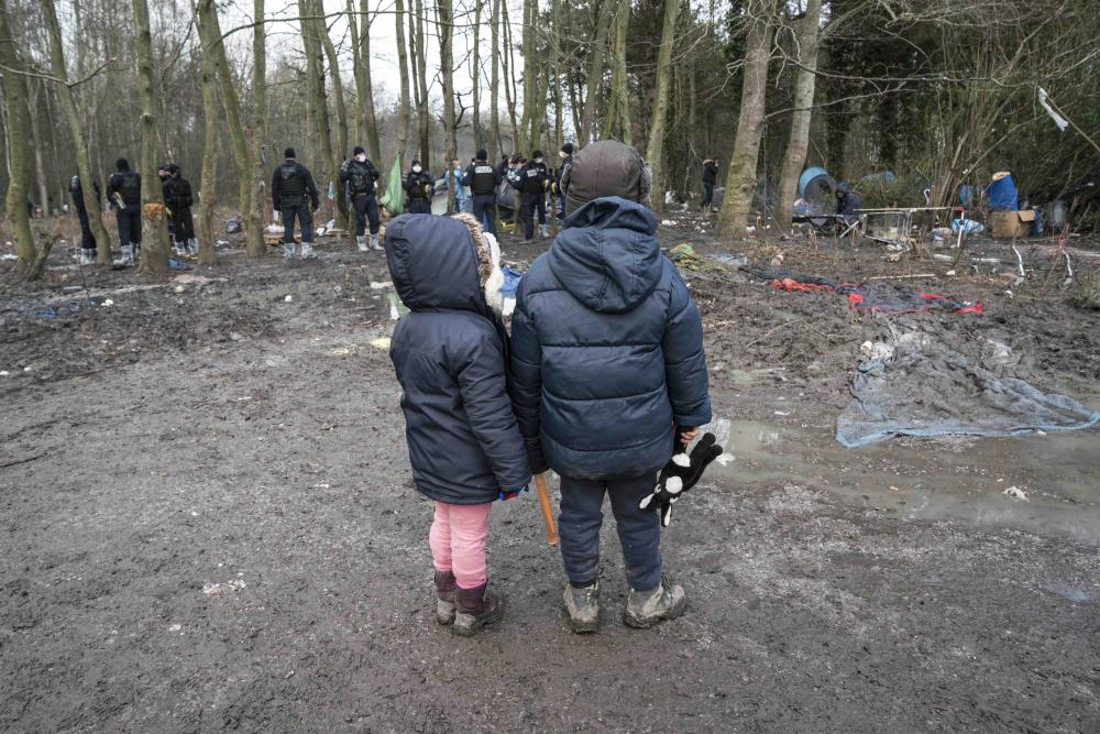 Two children wearing winter coats stand in a forest in front of a group of police officers