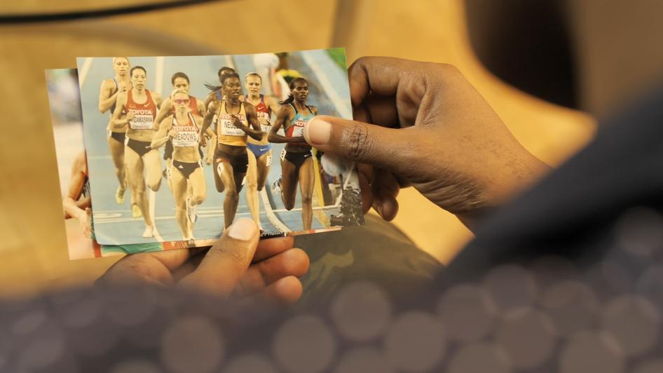 A woman holds a photo of a group of female runners competing