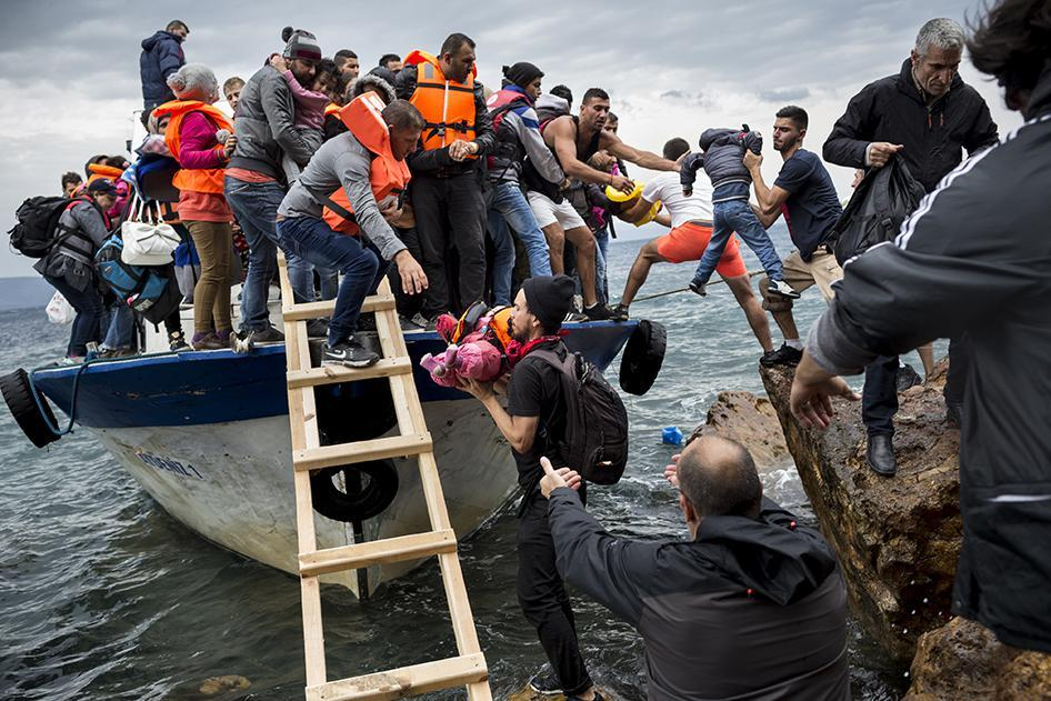 Asylum seekers and migrants descend from a large fishing vessel used to transport them from Turkey to the Greek island of Lesbos. October 11, 2015.