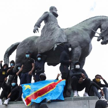 Demonstrators stand on the statue of Leopold II as one of them holds a national flag of the Democratic Republic of Congo during a protest for the end of racial injustice in Brussels, Belgium, June 7, 2020.