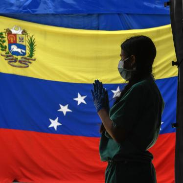 A staff member of Doctors Without Borders prepares herself as she waits for patients to be tested for Covid-19 in front of a Venezuelan flag at the Perez de Leon Hospital in the Petare neighbourhood, in eastern Caracas on June 23, 2020, amid the new coronavirus pandemic.