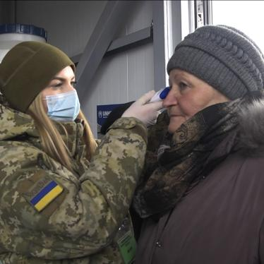 A soldier in a face mask checks the temperature of an older woman at a checkpoint in Mayorsk, Donetsk region, Ukraine, Monday, March 16, 2020.