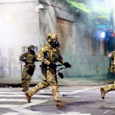 Federal officers run after dispersing protesters in Portland, Oregon, July 22, 2020.