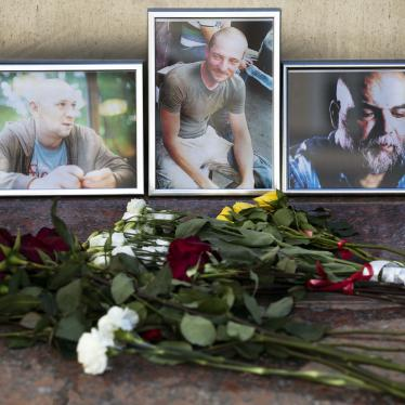 Flowers are placed by portraits of slain journalists Alexander Rastorguyev, Kirill Radchenko, and Orkhan Dzhemal, at the Russian Journalists' Union building in Moscow on August 1, 2018.