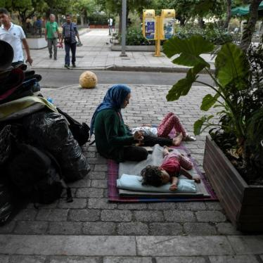 A woman sits with her children in Victoria Square in Athens, Greece, awaiting transfer after being evicted from their place of residence, July 20, 2020.