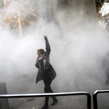 On December 30, 2017, a university student attends a protest inside Tehran University while a smoke grenade is thrown by anti-riot Iranian police, in Tehran, Iran.