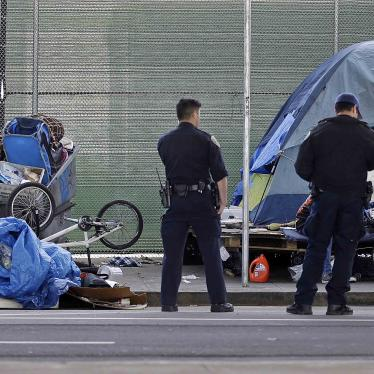 Police officers wait while people experiencing homelessness collect their belongings during a sweep of their encampment under a San Francisco, California freeway, March 1, 2016.