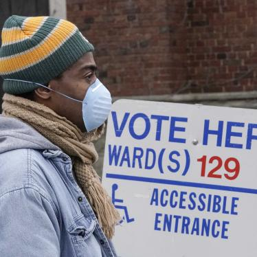 "A man in a beanie and face mask stands in front of a sign that says ""Vote Here"""