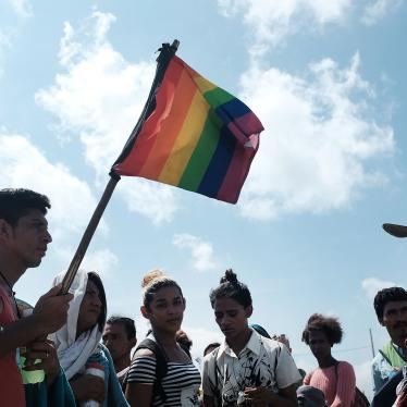 A group of men and women march walk while holding rainbow pride flags
