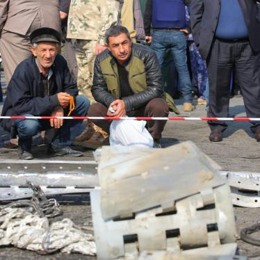 Residents of Barda examine the remnants of a Smerch cluster munition rocket