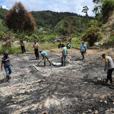 Villagers and police officers clean up debris at the site of suspected militant attack in Lembantongoa village in Sulawesi, Indonesia, November 30, 2020.