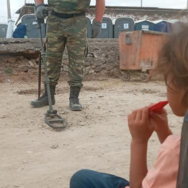 A girl from Syria living in Mavrovouni camp watches the Greek military search for unexploded munitions