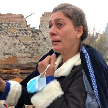 Shaira Guliyeva, 47, stands in front of her destroyed home and shows a photograph of her nephew, Arthur Guliyev, 13, who was killed there by a ballistic missile attack on October 17.