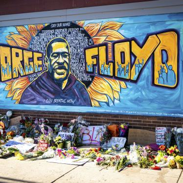 A mural dedicated to George Floyd and honoring the black lives matter movement, showing a depiction of George Floyd's face with his name and supporters of the movement against a blue painted background. Flowers and handwritten signs adorn the sidewalk beneath the mural.