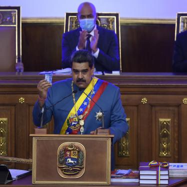Venezuela's Nicolás Maduro holds a copy of the constitution during his annual address to the nation before lawmakers at the National Assembly in Caracas, Venezuela, Tuesday, Jan. 12, 2021.