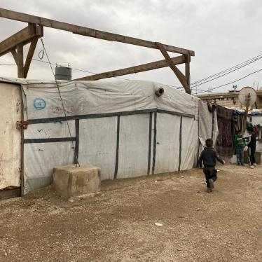 Children play next to shelters in a Syrian refugee camp in Arsal, Lebanon. Around 15,000 Syrian refugees in Arsal are entering their second winter without adequate roofs and insulation since the 2019 directive ordered them to dismantle concrete shelters and rebuild the top portion with tarp and wood. November 2020.