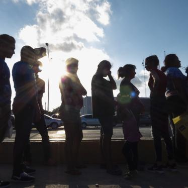 Migrants seeking asylum wait in line with their case paperwork to meet with an attorney on Oct. 5, 2019, during a weekly trip by volunteers, lawyers, paralegals and interpreters to the migrant campsite outside El Puente Nuevo in Matamoros, Mexico.