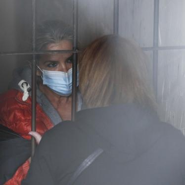 Standing behind bars, Bolivia's former interim President Jeanine Añez speaks to an unidentified woman at a police station jailhouse, in La Paz, Bolivia, on March 13, 2021.