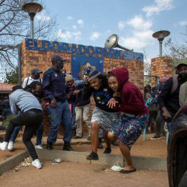 Protesters run for cover as they clash with police at Eldorado Park police station in Johannesburg, South Africa, August 27, 2020.