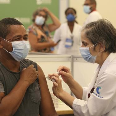 A white female healthcare professional wearing a mask, applying the covid-19 vaccine to a black male healthcare professional, wearing a mask, who is smiling