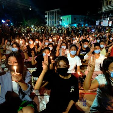 Protesters flash the three-fingered salute and hold candles during a rally at night in Yangon, Myanmar, March 14, 2021.