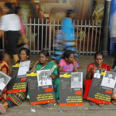 In this April 6, 2015, file photo, Sri Lankan ethnic Tamil women sit holding placards with portraits of their missing relatives as they protest out side a railway station in Colombo, Sri Lanka.