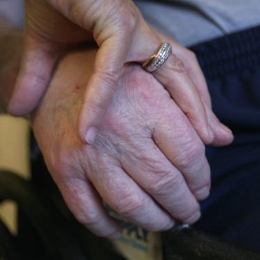 A nursing home resident holds his wife's hand.