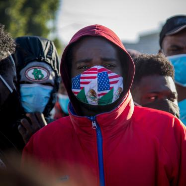A migrant from Haiti wearing a mask in the colors of the Mexican and US flags stands at a border crossing with others, waiting to asylum in the US, February 19, 2021.