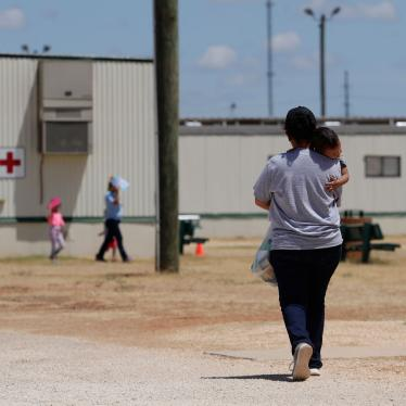 A woman walks carrying her child at the US Immigration and Customs Enforcement (ICE) South Texas Family Residential Center, in Dilley, Texas, August 23, 2019.