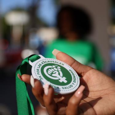 "An abortion rights activist holds a plastic medallion reading ""For the #3Causales (#3LegalGrounds), Life, Health and Dignity"" during a protest to urge parliament to approve a proposed reform to the penal code that could end the total ban on abortion, in Santo Domingo, Dominican Republic March 18, 2021."