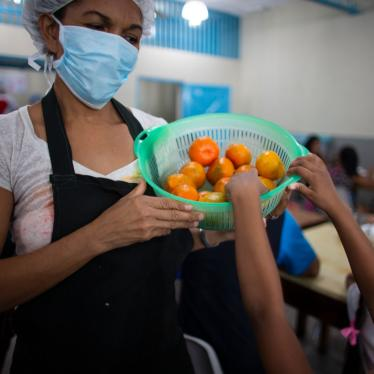 A girl reaches for a tangerine at a soup kitchen in Petare, Venezuela, February 27, 2020.