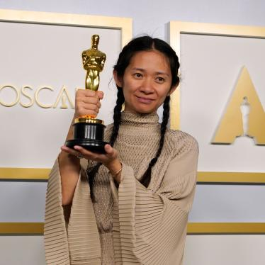 Director Chloe Zhao smiles and holds her golden Oscars statue after winning the award for Best Director