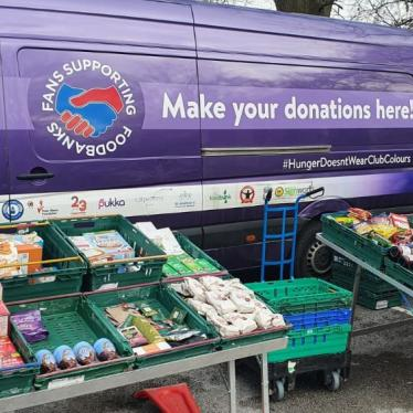 A mobile food pantry with food collected by Fans Supporting Foodbanks and other local anti-poverty groups set up at at St. Mary's Millennium Centre, Liverpool, UK. Photo shows a purple van with cases of food set up in front of it.