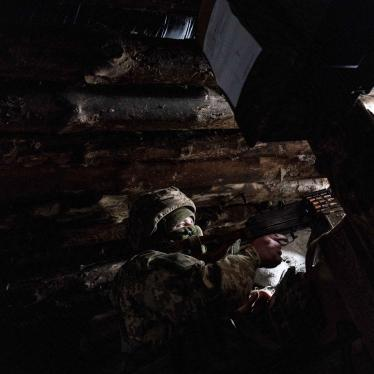 A Ukrainian soldier watches guard with a machine gun in his shelter near the front-line town of Krasnohorivka, eastern Ukraine