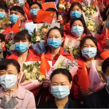 Image of people wearing face masks and holding Chinese flags and brightly-colored flowers.