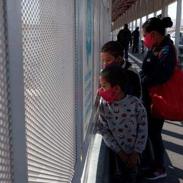 An asylum seeking family from Guatemala stands on the Paso del Norte international bridge. After border agents turned the family away at the port of entry, the family swam across the Rio Grande.