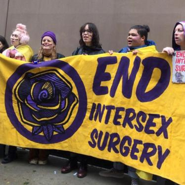 "People hold a yellow banner reading ""End Intersex Surgeries"" in purple writing"