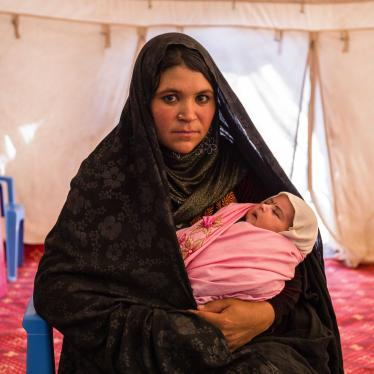 A woman holding a baby poses for the camera inside a large tent
