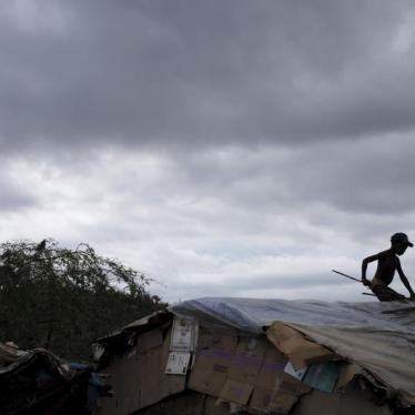 A boy fixes the roof of a makeshift tent at a refugee camp for Haitians returning from the Dominican Republic on the outskirts of Anse-a-Pitres, Haiti, September 6, 2015.