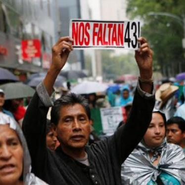 A protester holds up a sign next to relatives of some of the 43 missing students of Ayotzinapa College Raul Isidro Burgos during a march in Mexico City