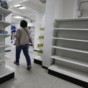 A woman walks past empty shelves at a drugstore in Caracas, February 23, 2016.