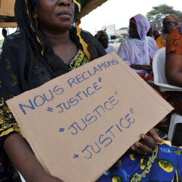 Victims of the 2010-11 post-election crisis hold placards reading 'We claim justice, justice justice' at a gathering in the Kouassai district of Abidjan on February 28, 2013, during the International Criminal Court's confirmation of charges hearing agains