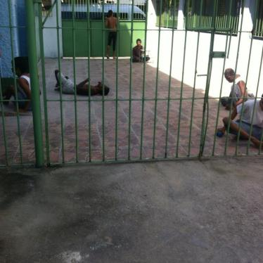 A group of persons with disabilities in a yard in an institution in Rio de Janeiro. Residents are taken outside for a few hours during the day but spend most of the time confined to their beds.
