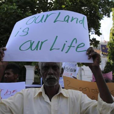 A Sri Lankan Tamil man holds a placard during a protest in Colombo on August 21, 2018, demanding the release of lands still occupied by the military.
