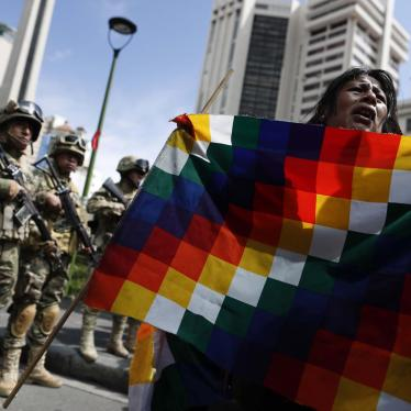 A demonstrator holds a Wiphala flag in front of soldiers blocking a street in downtown La Paz, Bolivia, Friday, Nov. 15, 2019.