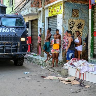 A military police armored vehicle passes by a person killed by police on April 7, 2016 in the Jacarezinho favela. Military police killed tow other people during the same raid.