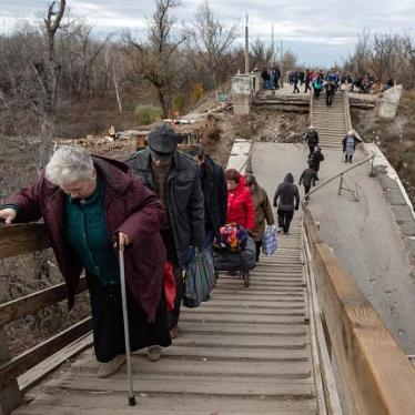Older people crossing the broken bridge at the Stanytsia Luhanska checkpoint.