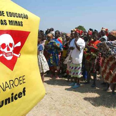 Villagers stand in front of a Unicef banner warning of landmines outside Caala, Angola