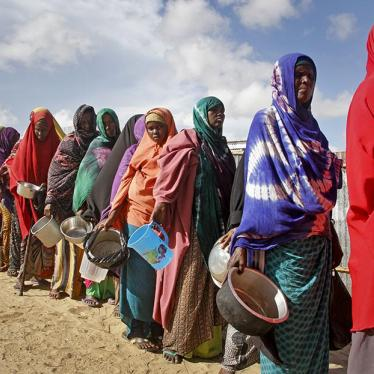 Women who fled drought line up to receive food distributed by local volunteers at a camp for displaced persons in the Daynile neighborhood on the outskirts of the Somalian capital Mogadishu