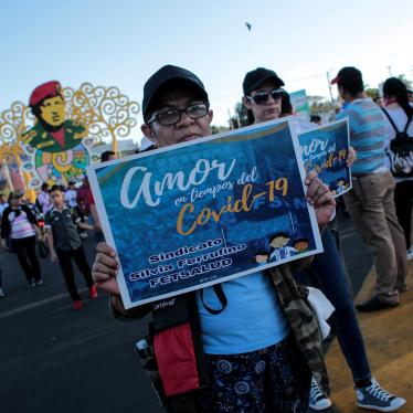 "A woman holds a sign that reads ""Love in Times of Covid-19"" during a government-sponsored march in Managua, Nicaragua, on March 14, 2020."